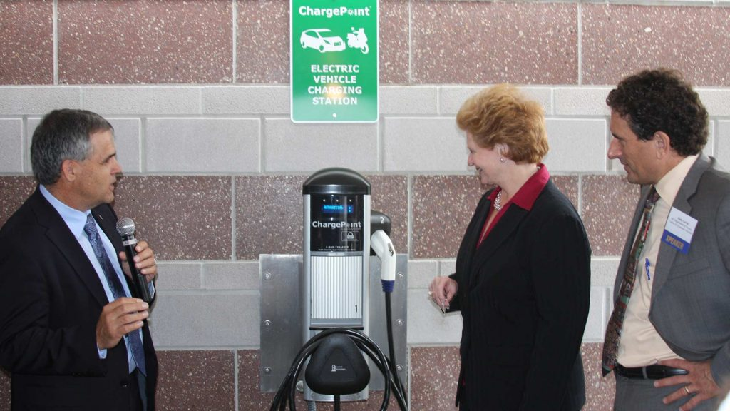 Debbie Stabenow and others next to a vehicle chargepoint