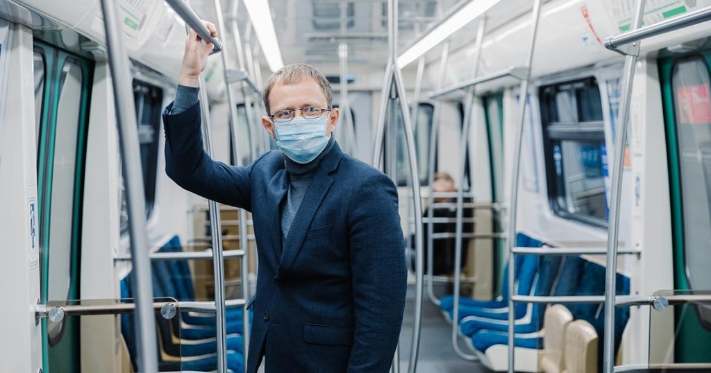 Man wearing a facemask and the lone passenger on a subway