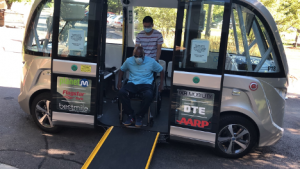 The Autonom shuttle with the driver assisting and elderly Detroit resident down a ramp
